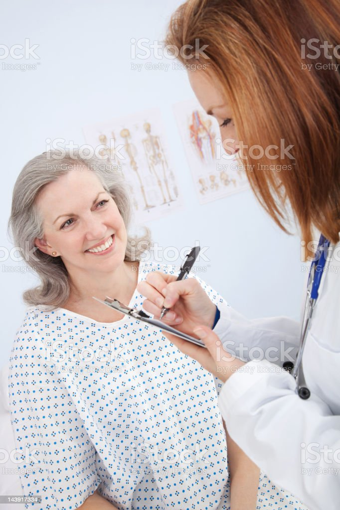 Happy Patient in Examination Room With Her Doctor royalty-free stock photo