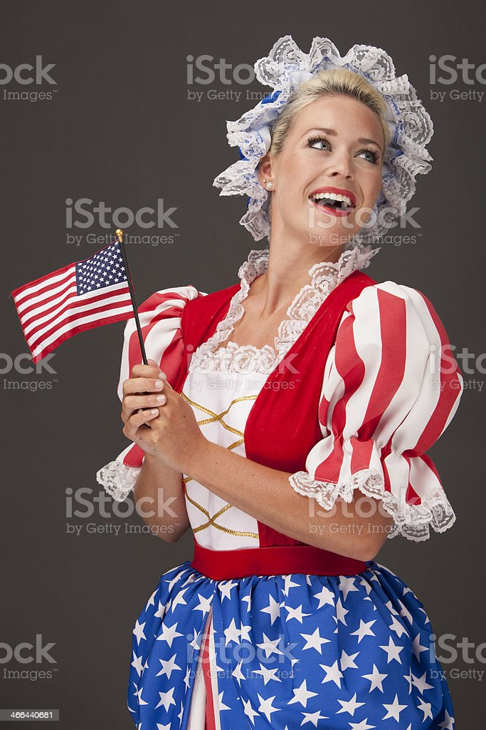 Happy patriotic woman holding an American flag royalty-free stock photo