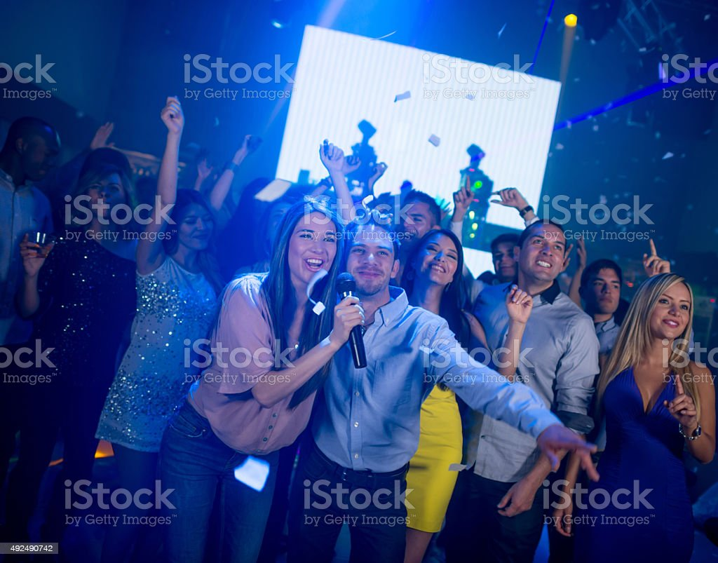 Happy people at a karaoke party stock photo