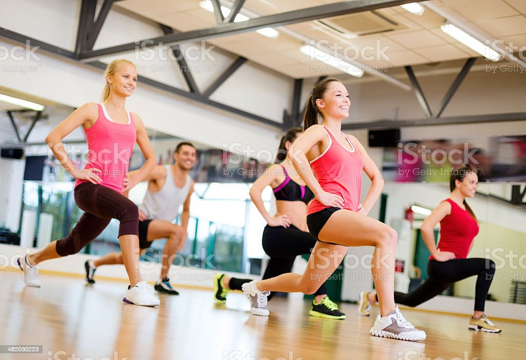 happy people doing lunge exercise in gym stock photo