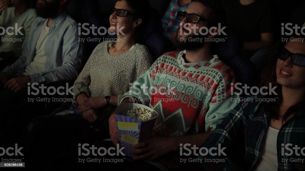 happy people enjoying in the cinema watching a 3d movie stock photo
