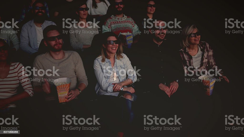 happy people enjoying in the cinema watching  movie stock photo