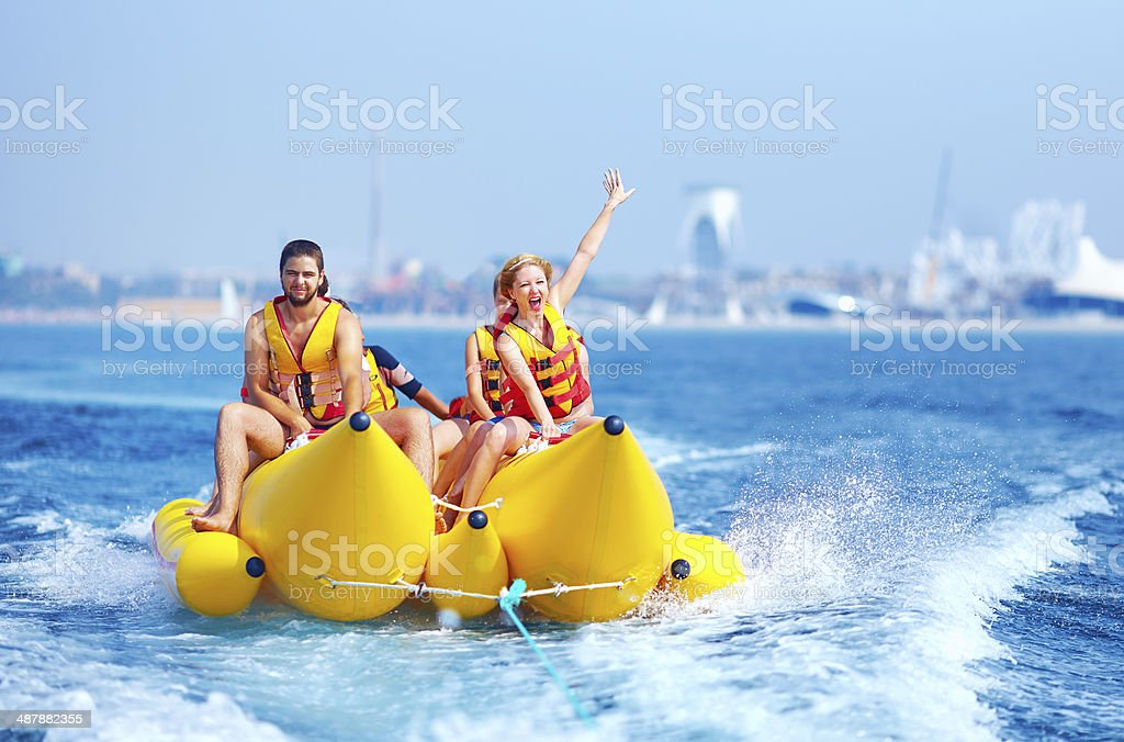 happy people having fun on banana boat stock photo