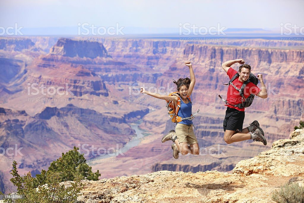 \'Happy people jumping in Grand Canyon. Young multiethnic couple on...