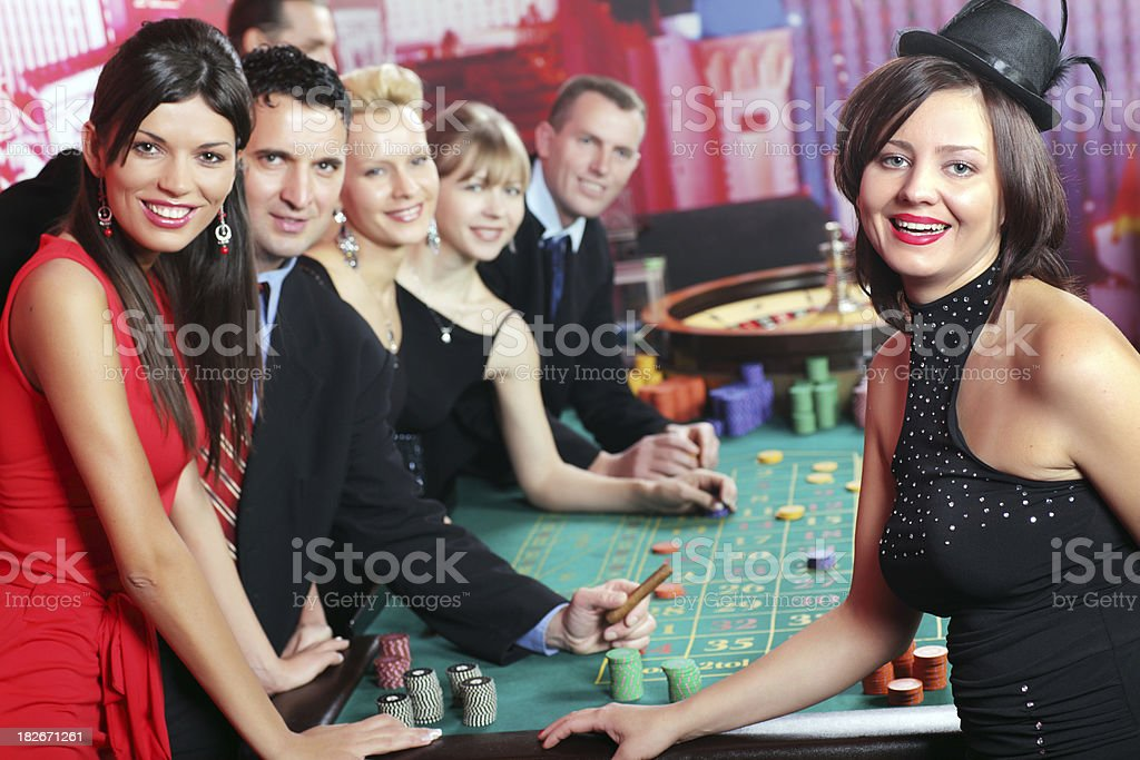 Happy people playing in real casino. stock photo