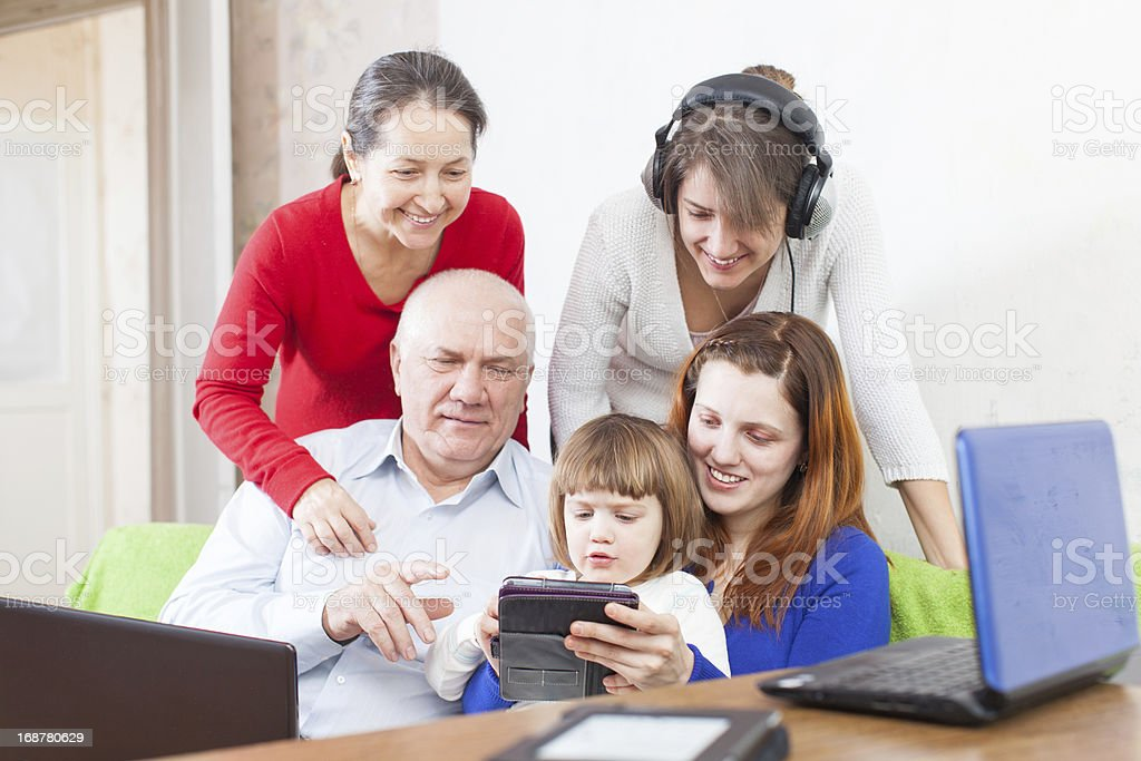 Happy  people  uses  various electronic devices in home royalty-free stock photo