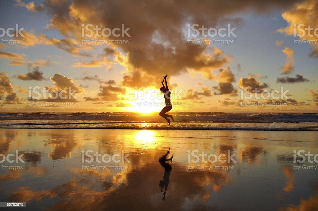 Happy person jumping into sunrise stock photo