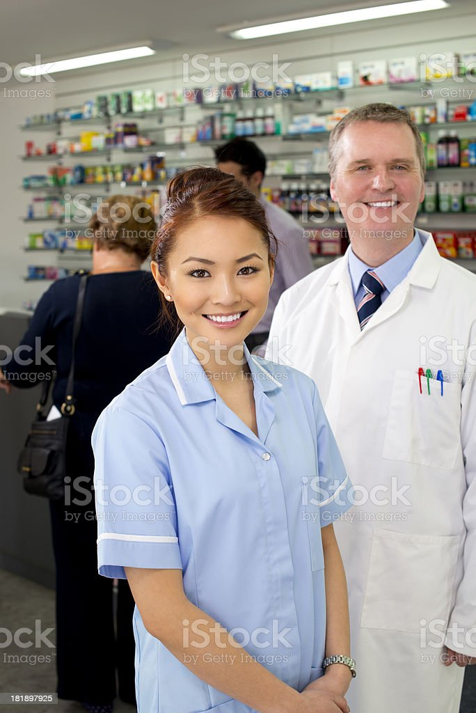 happy pharmacists in busy pharmacy royalty-free stock photo