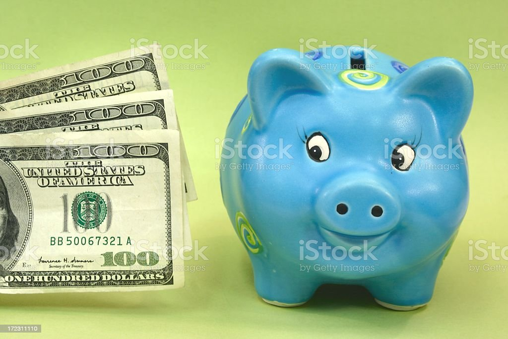 Happy Pig Series: blue piggy bank looking at money royalty-free stock photo