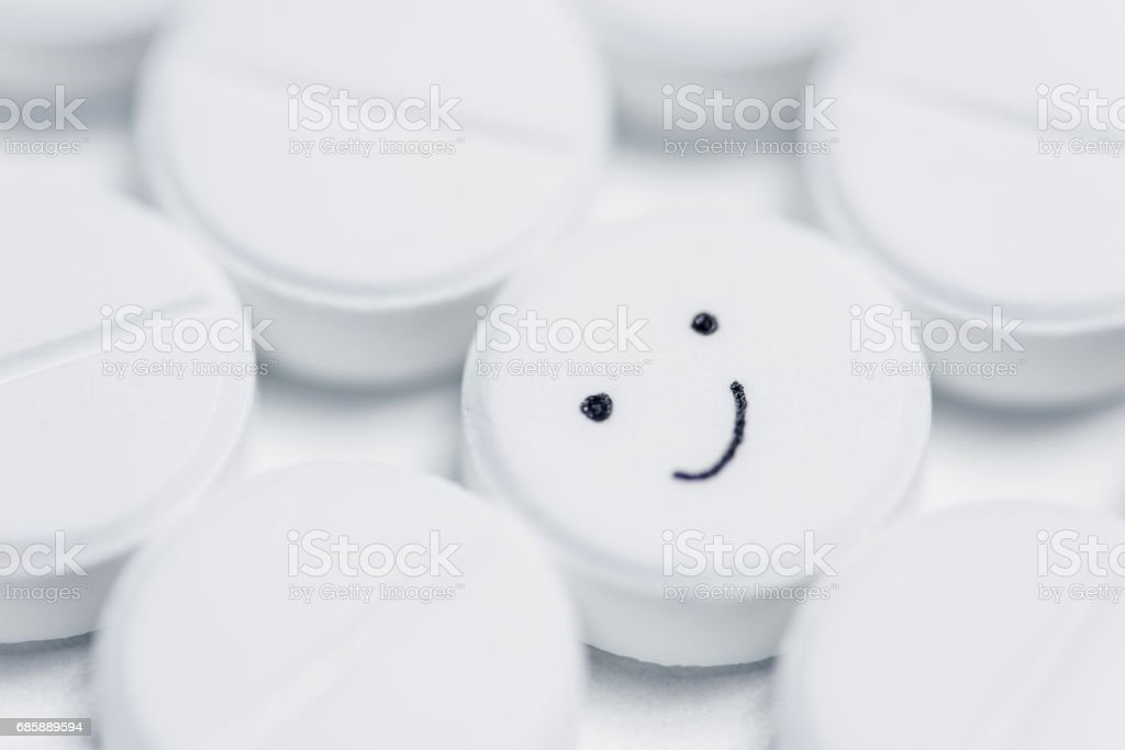 Happy pill surrounded by white prescription pills stock photo