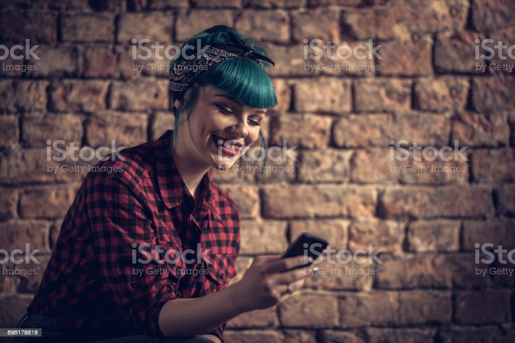 Beautiful retro styled woman texting on cell phone against brick wall.