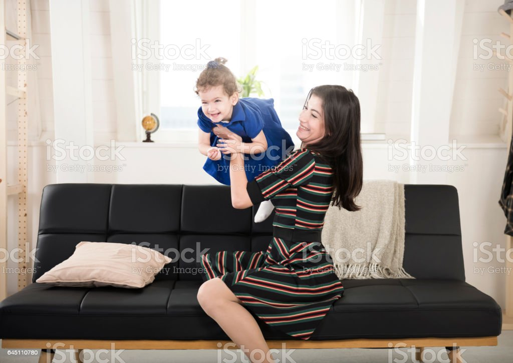 Happy playful mother and daughter having fun at home stock photo