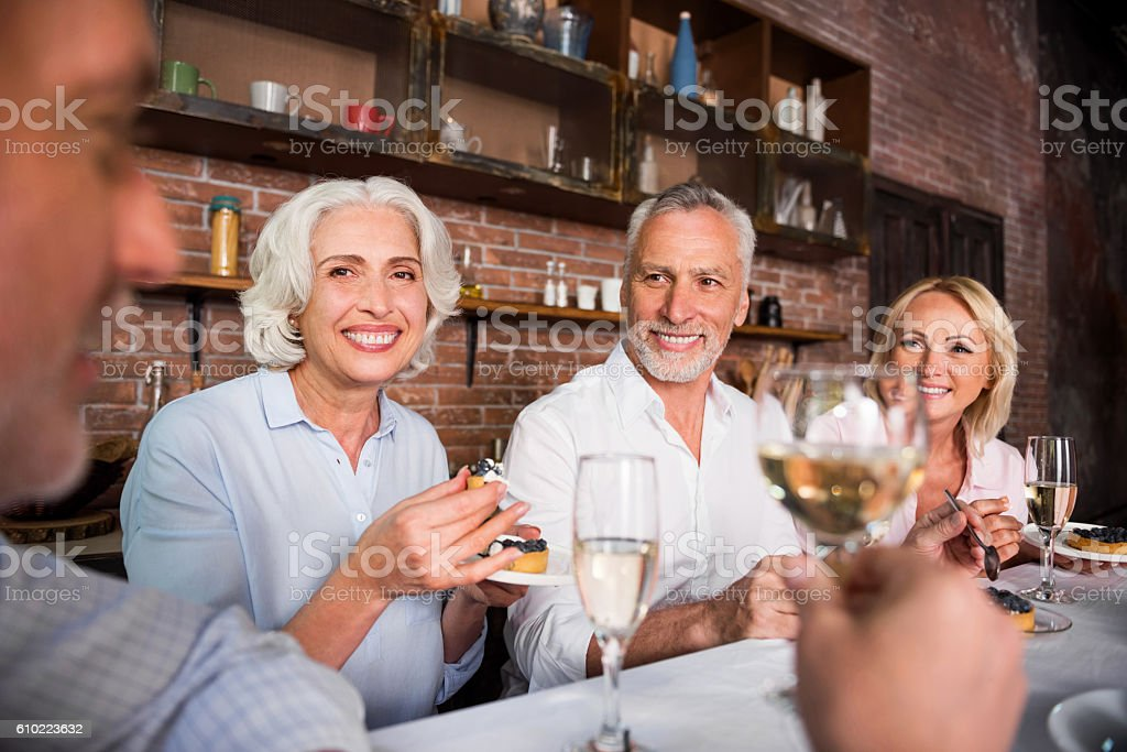 Happy pleasant people talking about wine round the table stock photo