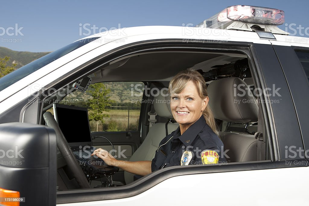 Happy Policewoman Driving Police Car on computer stock photo