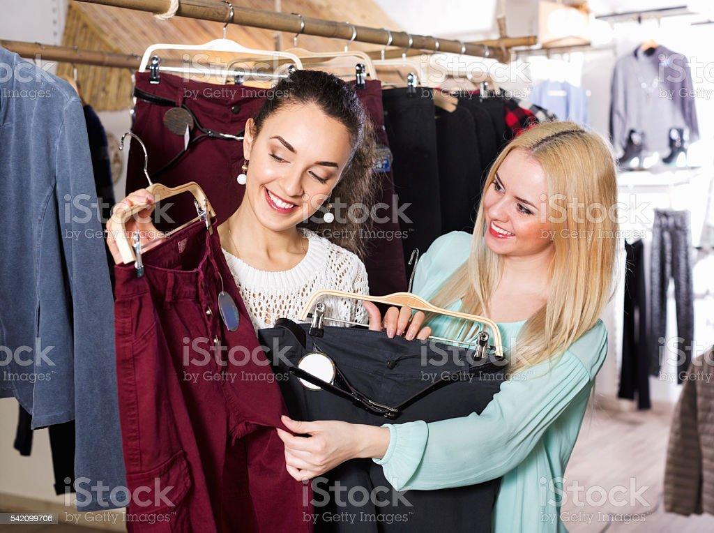 Happy positive female friends choosing trousers stock photo
