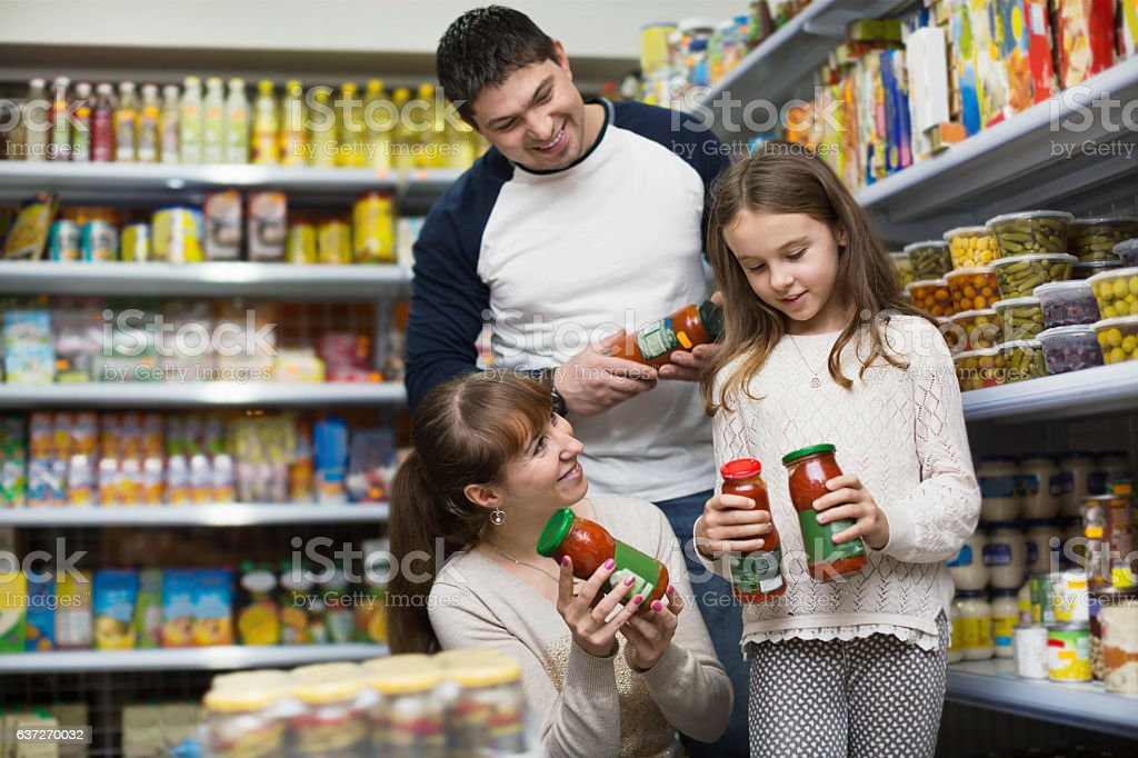 Happy  positive smiling parents with little girl buying tinned stock photo