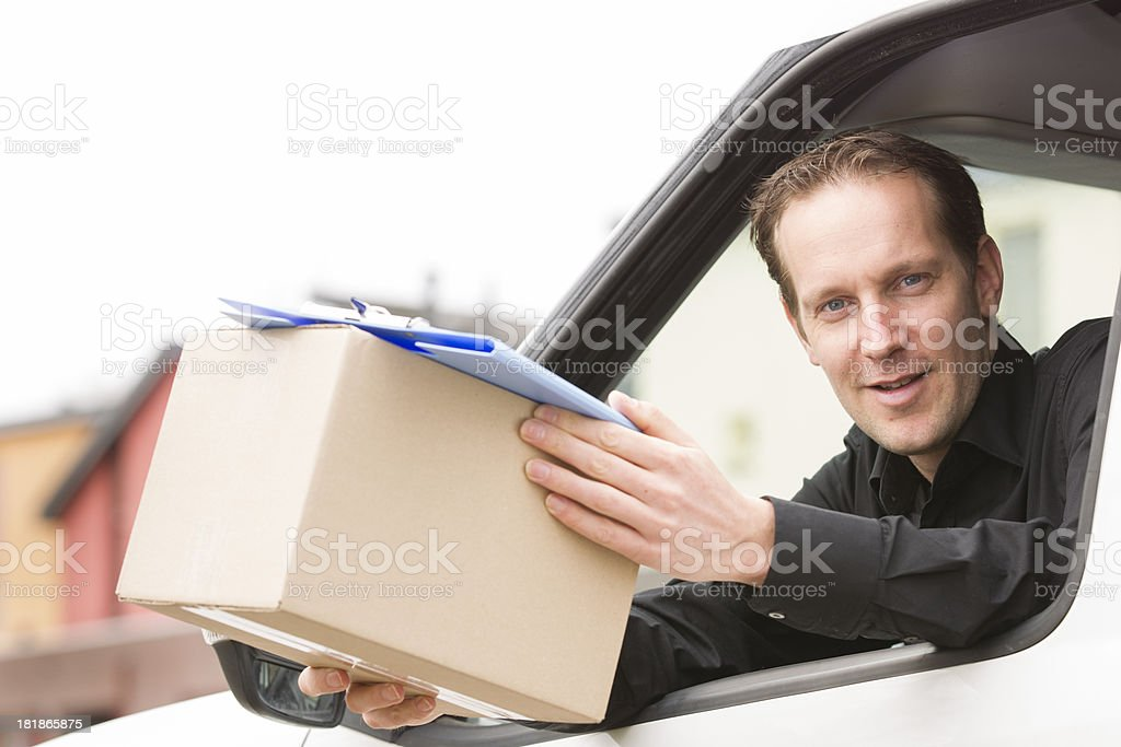 Happy postal delivery courier in a van delivering package stock photo