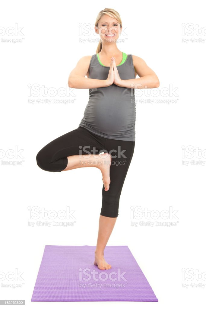 Happy pregnant balancing in yoga pose stock photo