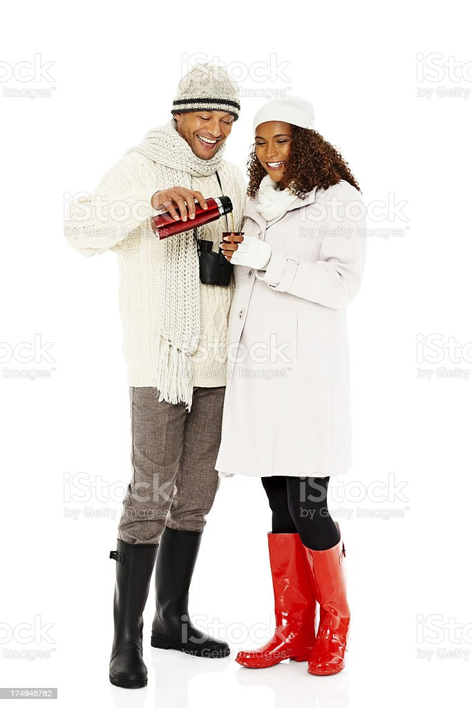 Happy pregnant couple in winter wear drinking hot coffee royalty-free stock photo