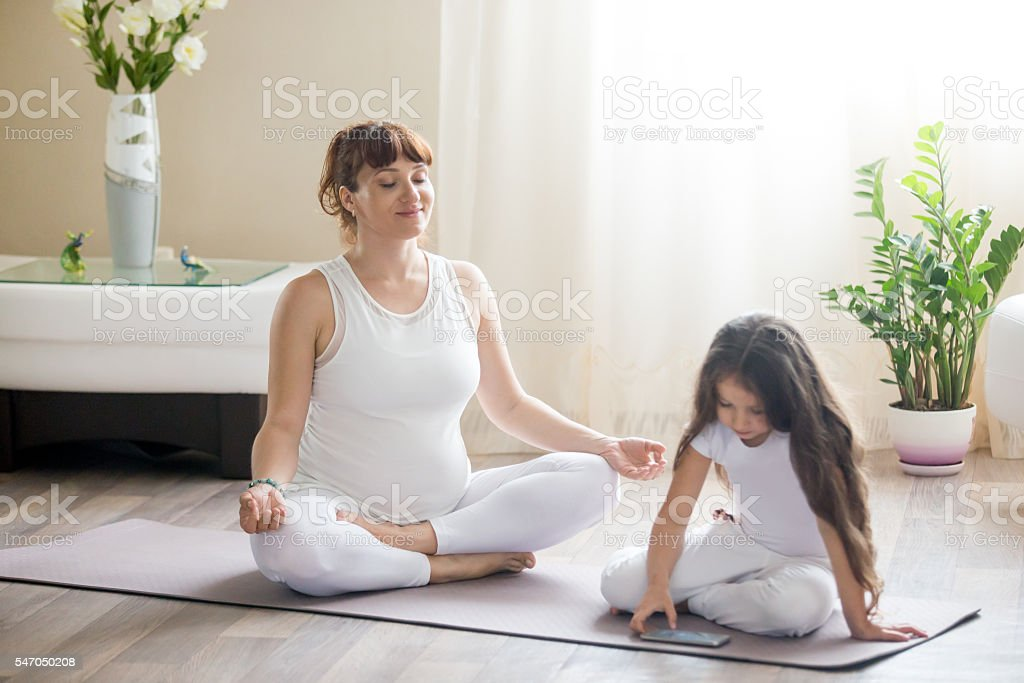 Happy pregnant mother and kid girl spending time together home stock photo