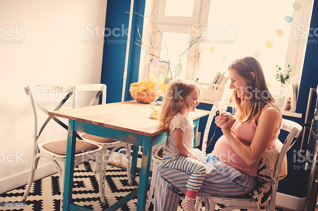 happy pregnant mother playing with toddler daughter at home stock photo