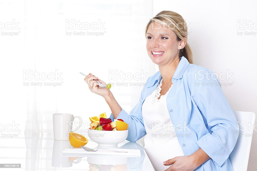 Happy pregnant woman eating fruit at the breakfast table royalty-free stock photo