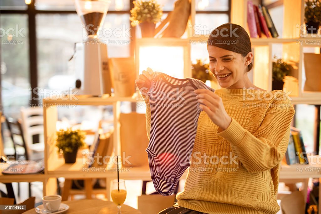 Happy pregnant woman looking at baby clothes in a cafe. stock photo
