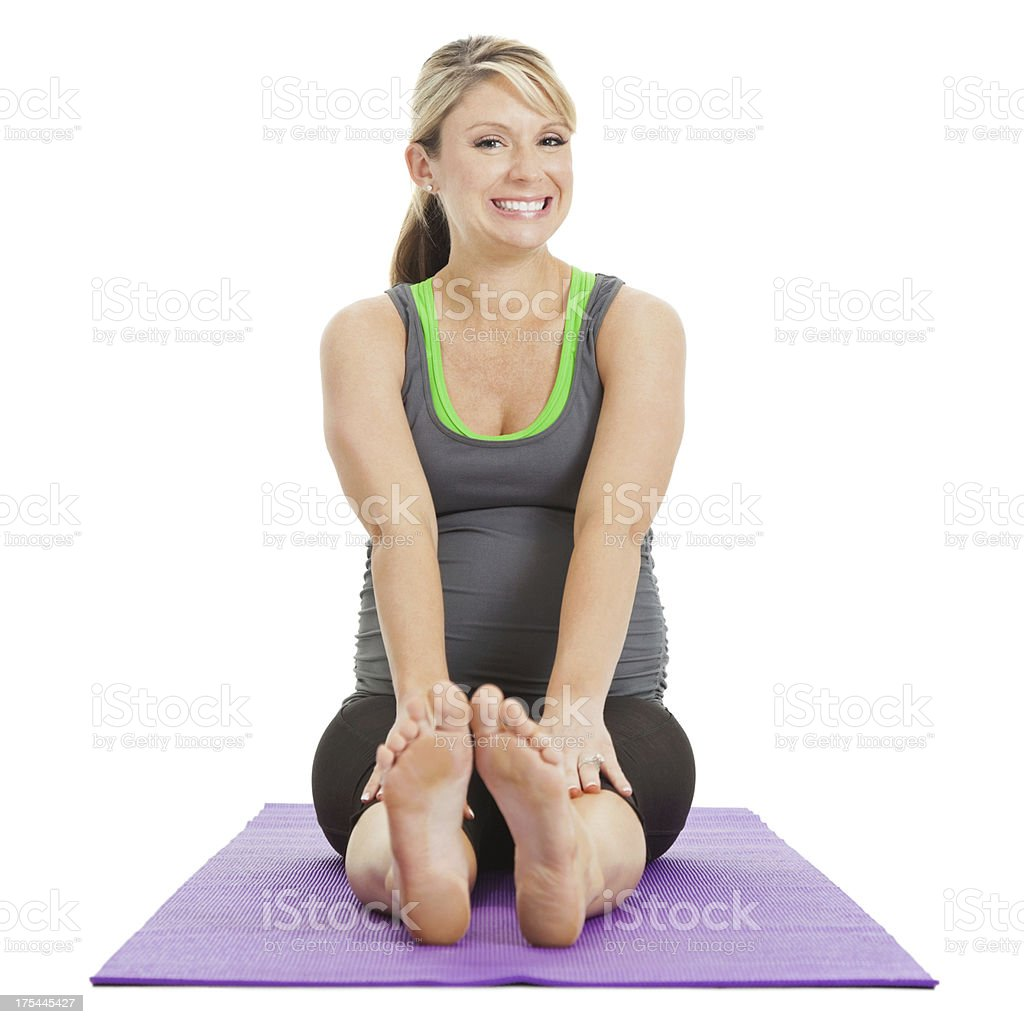 Happy pregnant woman stretching out on yoga mat stock photo