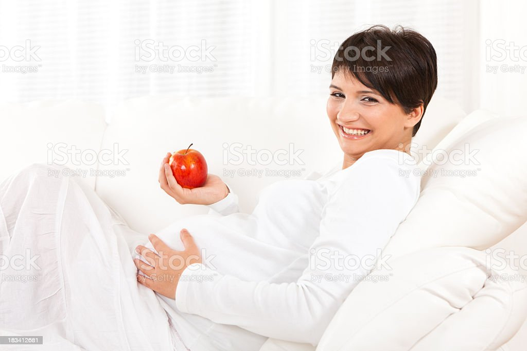 Happy pregnant woman with apple stock photo