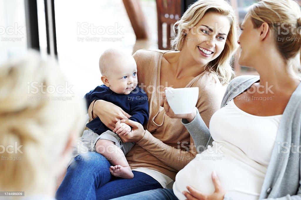 Happy pregnant woman with her friends relaxing at home stock photo