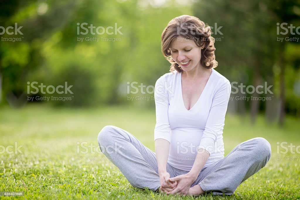 Happy pregnant woman working out in park. Copy space stock photo
