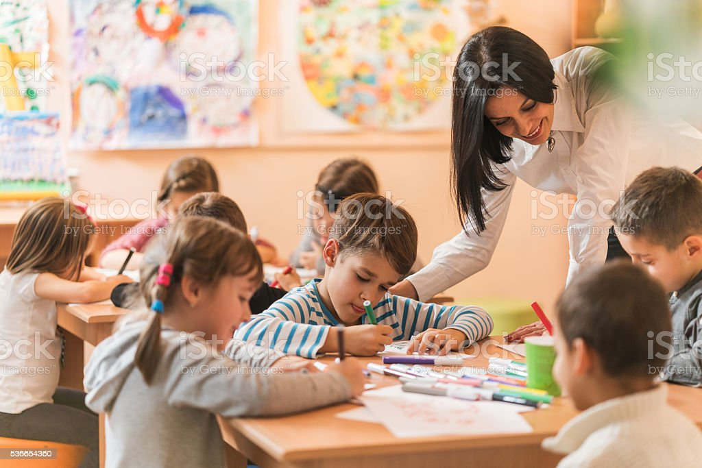 Young teacher helping small kids with their drawings in a preschool.