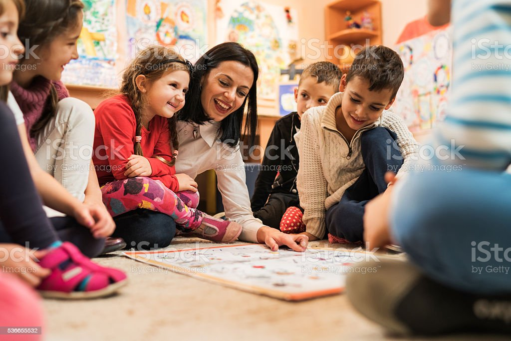 Happy preschool teacher educating large group of children in kindergarten. stock photo