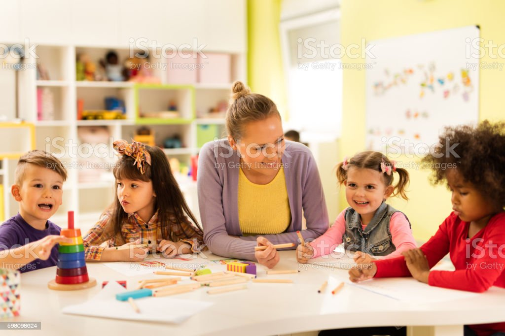 Smiling teacher drawing with group of children at kindergarten.