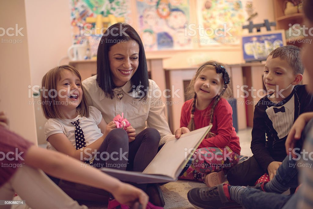 Happy preschool teacher telling stories to group of kids. stock photo