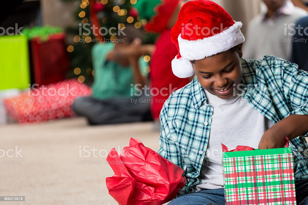 Happy preteen African American boy opening a Christmas gift stock photo
