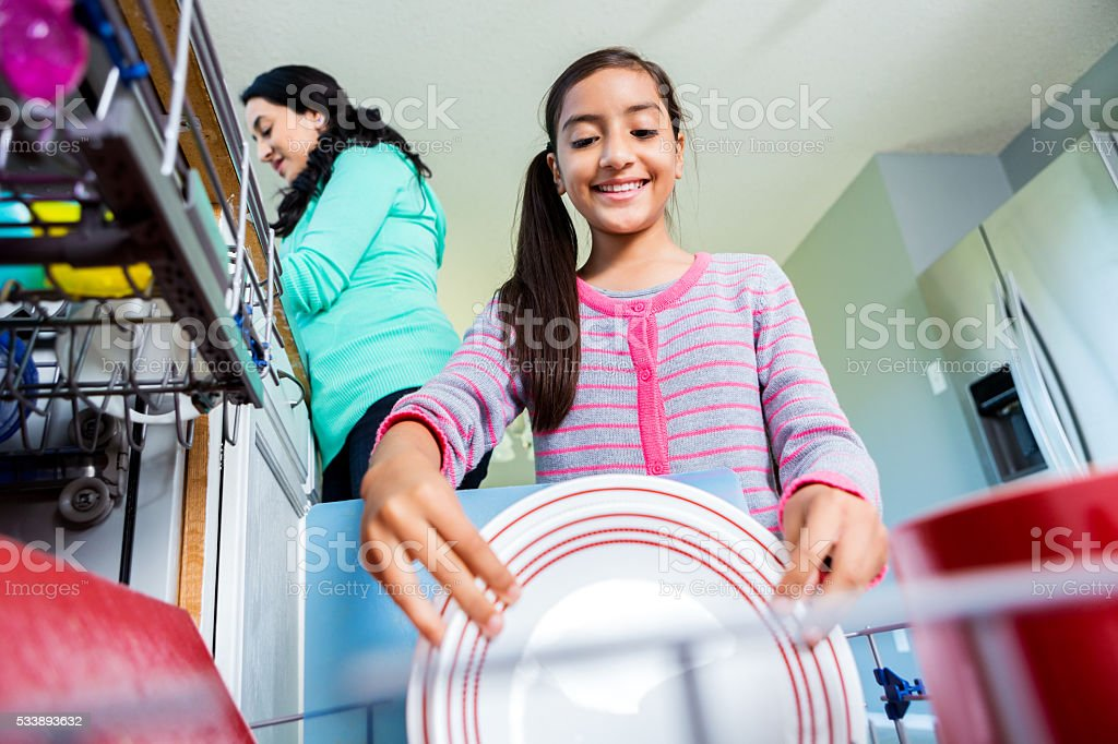 Happy pre-teen girl helps mom in the kitchen stock photo