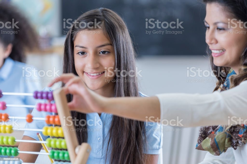 Happy preteen girl uses abacus at school stock photo