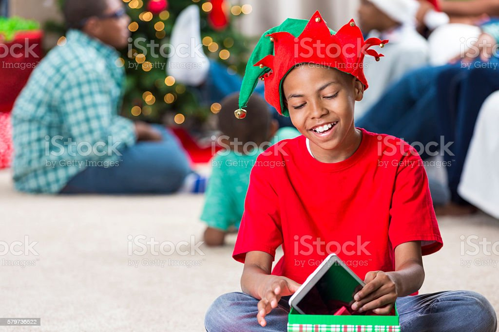 Happy pre-teen in elf hat gets tablet for Christmas stock photo