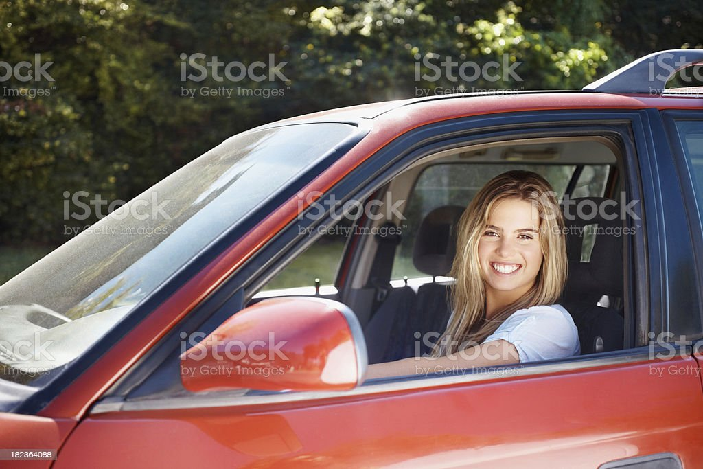 Happy pretty female driving her red car outdoors royalty-free stock photo
