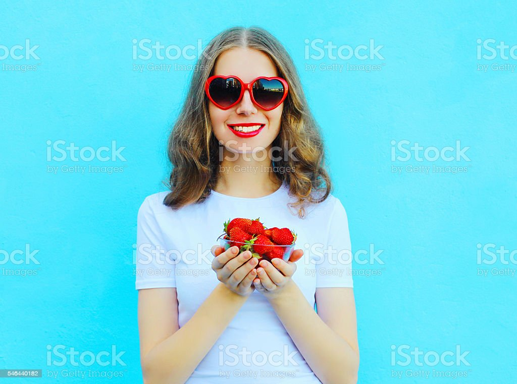 Happy pretty smiling woman with many strawberry over blue backgr stock photo