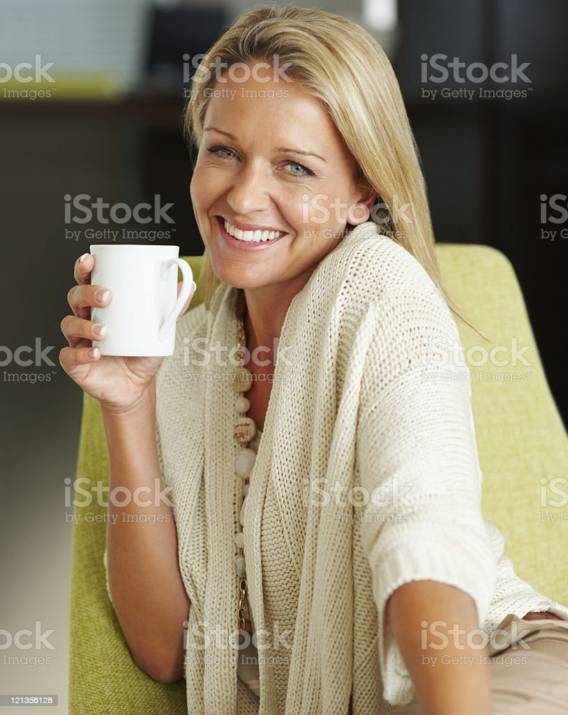 Happy pretty woman holding a cup of tea or coffee royalty-free stock photo
