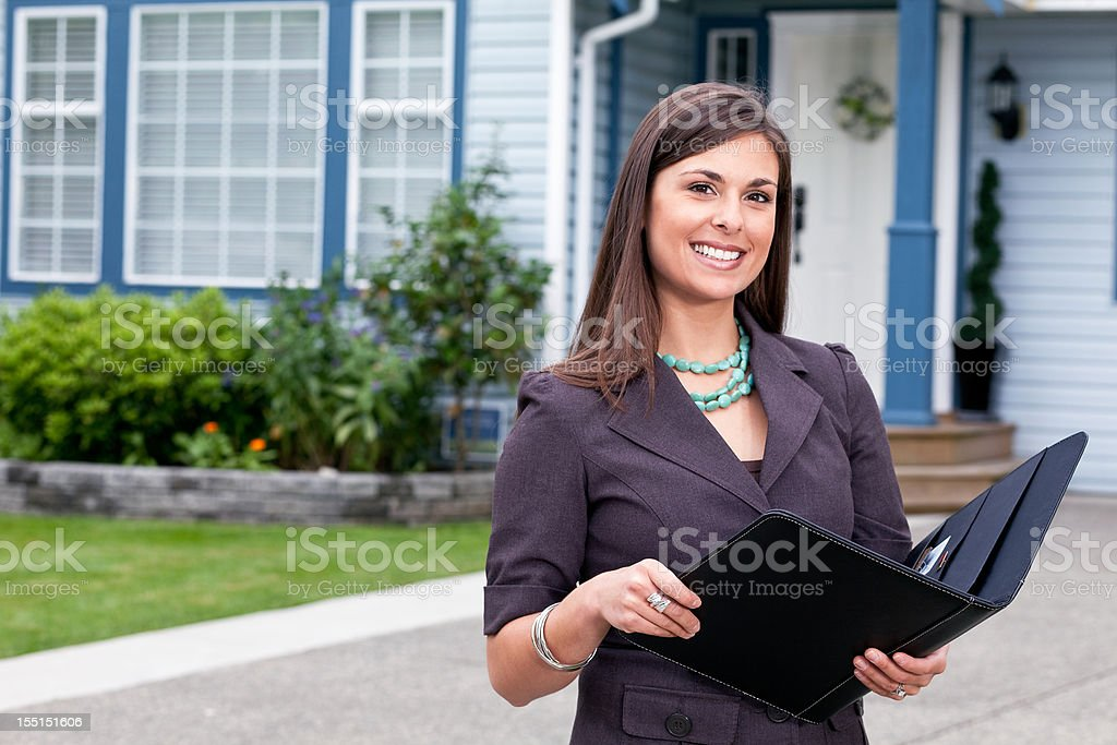 Happy professionally dressed woman holding organizer outside a house stock photo