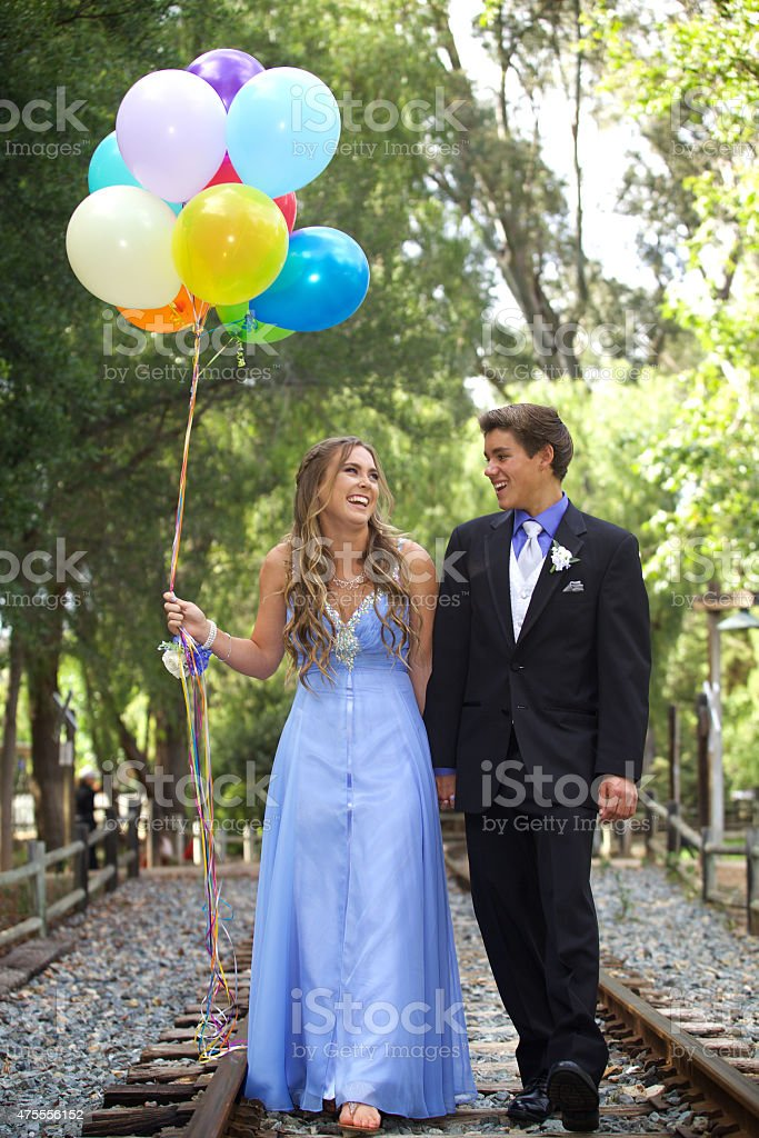 Happy Prom Couple Walking with Balloons stock photo