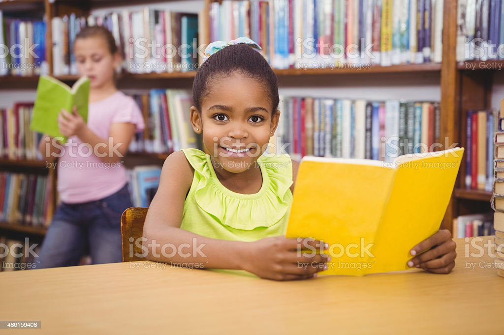 Happy pupil reading a library book stock photo
