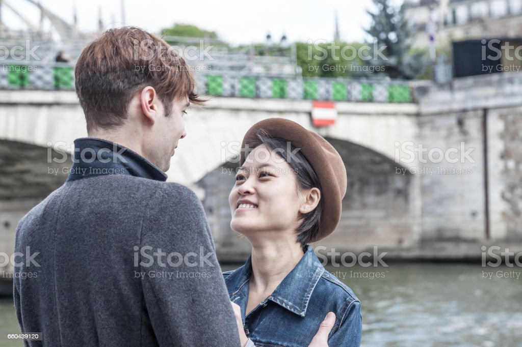 happy quirky Caucasian and oriental multiracial couple by river Seine in Paris stock photo