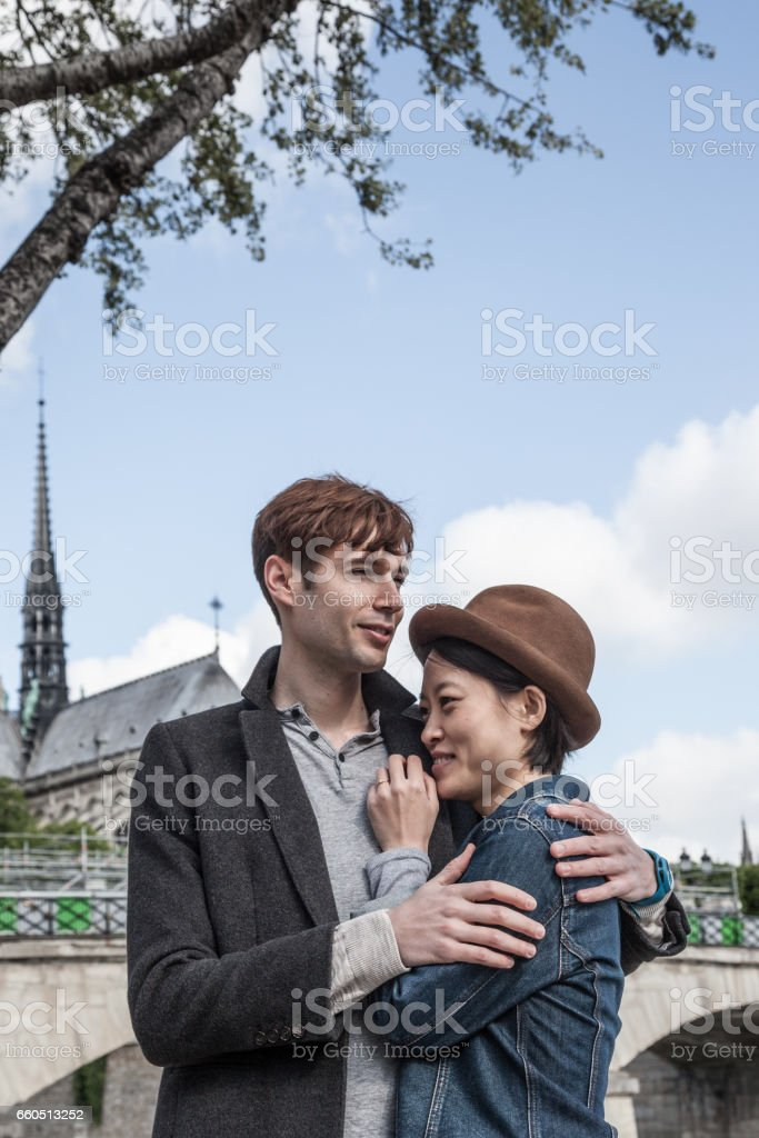 happy quirky Caucasian and oriental multiracial couple by river Seine near Notre Dame in Paris stock photo