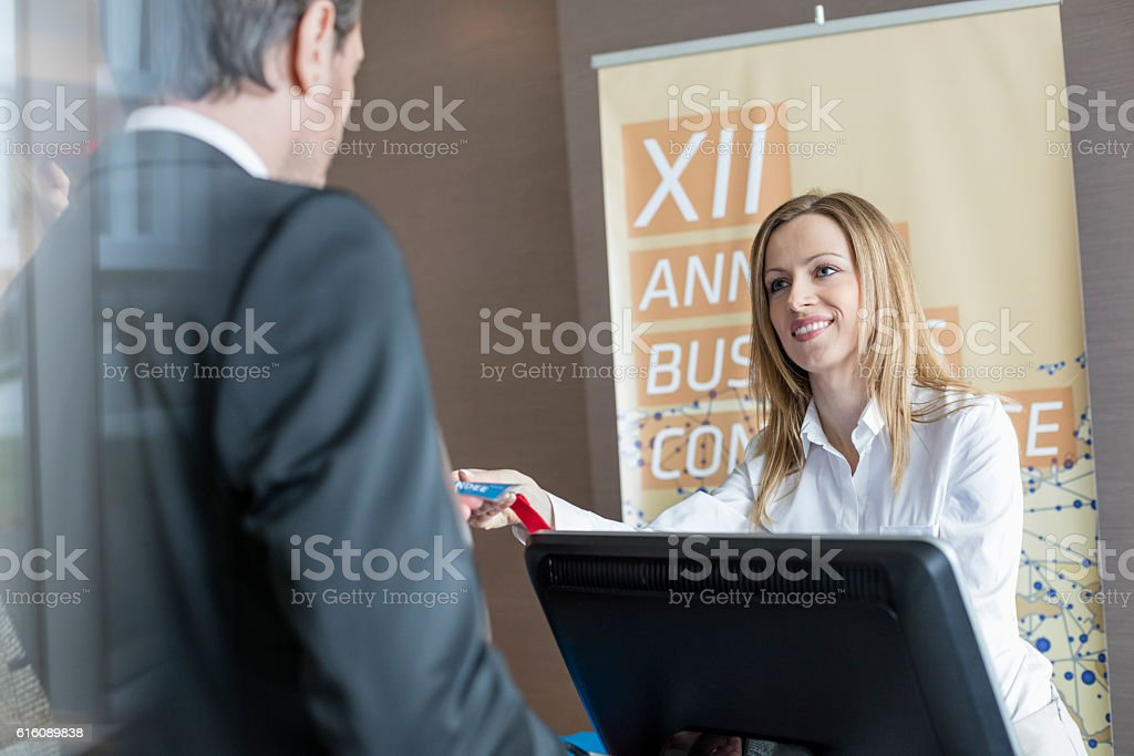 Happy receptionist giving identity card to businessman at convention center stock photo