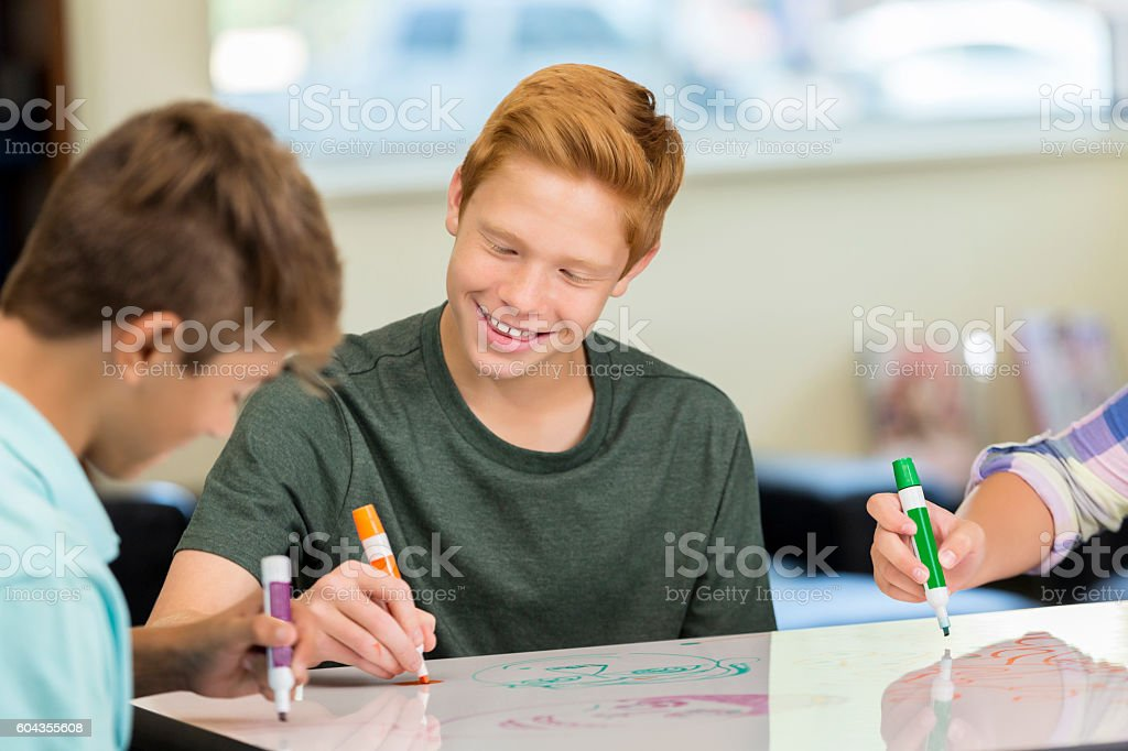 Happy red haired teenager working animation station of makerspace class stock photo