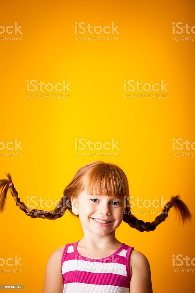 Happy, Red-Haired Girl with Upward Braids and a Smile stock photo